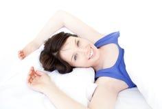 Primo piano di una donna sorridente che sveglia lentamente Fotografie Stock