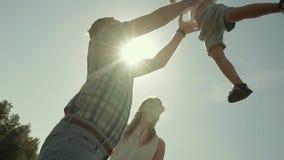 Primo piano di una famiglia di tre Generi il figlio di lancio su nell'aria, supporti felici della madre vicino archivi video