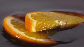 Primo piano di una fetta arancio deliziosa che cade nello sciroppo di cioccolato stock footage