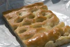 Primo piano di una fetta di focaccia, un pane italiano tipico su briciolo Fotografia Stock