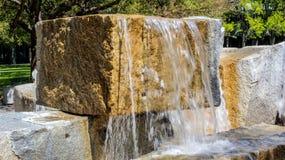 Primo piano di una fontana del blocchetto del granito un giorno soleggiato Immagini Stock