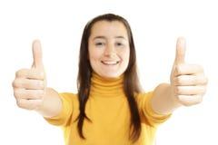 Primo piano di una giovane donna che mostra i pollici su Immagini Stock