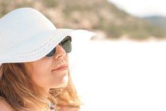 Primo piano di una giovane donna con luce solare degli occhiali da sole Fotografia Stock