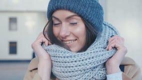 Primo piano di una giovane donna graziosa in un sorridere sveglio della sciarpa e del cappello stock footage