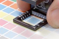 Primo piano di una lente di ingrandimento e di una mano su una stampa di prova variopinta Immagine Stock
