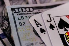 Primo piano di una mano del black jack 21 su un letto di cento banconote in dollari II BASSO Fotografie Stock Libere da Diritti