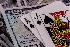 Primo piano di una mano del black jack 21 su un letto di cento banconote in dollari III Fotografia Stock