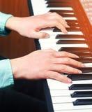 Primo piano di una mano del ` s dell'esecutore di musica che gioca il piano, ` s ha dell'uomo immagini stock libere da diritti
