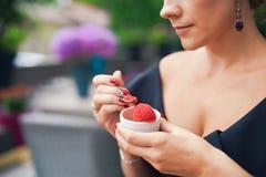 Primo piano di una mano del ` s della donna che tiene una tazza con il gelato rosso casalingo Prima colazione, spuntini Il concet Immagini Stock