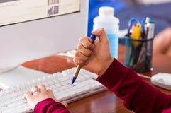 Primo piano di una mano femminile che tiene una penna in uno scrittorio con un computer perdere tempo concetto Immagine Stock Libera da Diritti