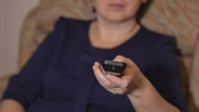 Primo piano di una mano femminile con un telecomando su un fondo di una donna in un vestito blu fotografia stock