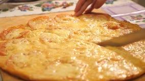 Primo piano di una persona che affetta una pizza di merguez in fette multiple con una taglierina della pizza video d archivio