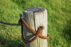 Primo piano di una posta di legno legata con un cavo arrugginito davanti ad un campo erboso Immagine Stock