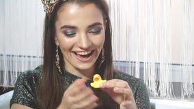 Primo piano di una ragazza che ride nella sorpresa che gioca con l'anatra di gomma stock footage