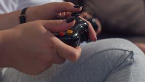 Primo piano di una ragazza con un bambino che gioca i video giochi con le leve di comando in loro mani video d archivio