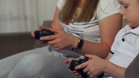 Primo piano di una ragazza con un bambino che gioca i video giochi con le leve di comando in loro mani stock footage