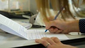Primo piano di una scrittura femminile della mano su un taccuino in bianco con una penna Primo piano di una scrittura femminile d Immagine Stock