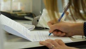 Primo piano di una scrittura femminile della mano su un taccuino in bianco con una penna Primo piano di una scrittura femminile d Fotografia Stock Libera da Diritti