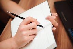 Primo piano di una scrittura femminile della mano su un taccuino in bianco con una penna fotografia stock libera da diritti
