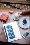 Primo piano di una tavola con un computer portatile, un dolce e un latte Vista da sopra immagine stock