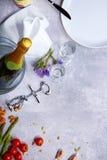 Primo piano di una tavola grigia con il piatto, una bottiglia di champagne, pomodori, asparago, vetri, cavaturaccioli su un fondo Immagini Stock
