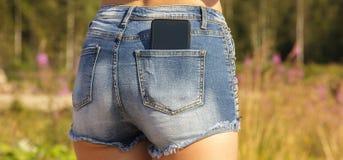 Primo piano di uno smartphone nero nella tasca posteriore dei jeans del ` una s della ragazza Fotografia Stock Libera da Diritti