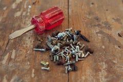 Primo piano di vecchia vite del cacciavite i bulloni sulla tavola Fotografia Stock