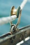 Primo piano di vecchio blocchetto d'annata dell'yacht del metallo con la corda, usato a Immagine Stock