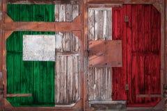 Primo piano di vecchio portone del magazzino con la bandiera nazionale fotografia stock libera da diritti