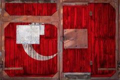 Primo piano di vecchio portone del magazzino con la bandiera nazionale fotografia stock