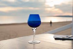 Primo piano di vetro blu sulla spiaggia romantica di tramonto Fotografie Stock Libere da Diritti