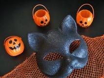 Primo piano di vista superiore della maschera del gatto di Halloween di divertimento e presa-o-lanterne mini di risata sul contes Fotografie Stock Libere da Diritti
