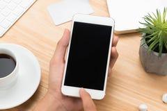 Primo piano a disposizione facendo uso del telefono Derisione di Smartphone sul modello sopra fuori fotografie stock