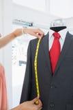 Primo piano estremo delle mani che misurano vestito sul manichino Immagini Stock