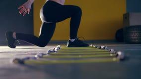 Primo piano, gambe femminili in ghette nere e scarpe da tennis la donna si esercita con una scala del piede dell'atleta, salti video d archivio