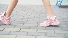 Primo piano gambe femminili in scarpe da tennis rosa alla moda ragazza che cammina sulla via con pavimentazione Luce del giorno s video d archivio