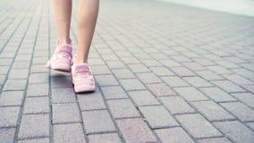 Primo piano gambe femminili in scarpe da tennis rosa alla moda ragazza che cammina sulla via con pavimentazione Luce del giorno s stock footage