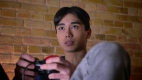 Primo piano giù sul ritratto di giovane maschio coreano che gioca i video giochi e che è eccitato all'interno video d archivio