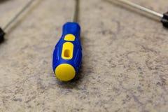Primo piano giallo blu del cacciavite del ferro della penna di plastica su un'elettricità manuale di riparazione dello strumento  fotografia stock