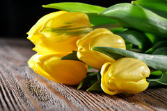 Primo piano giallo dei tulipani su fondo di legno rustico Fotografie Stock