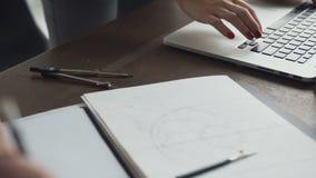 Primo piano Giovane architetto femminile che lavorano con un computer portatile e modelli che si trovano sul desktop nell'ufficio archivi video