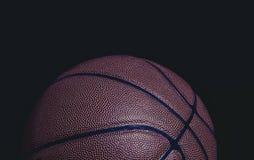 Primo piano Grungy di pallacanestro mezza su un fondo nero immagine stock libera da diritti