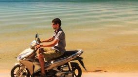 Primo piano Guy Drives Motorbike dopo la palma lungo la spiaggia alle barche stock footage