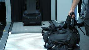 Primo piano i passeggeri prendono le loro borse, bagaglio dal nastro trasportatore, dopo che hanno passato l'analizzatore dei bag archivi video