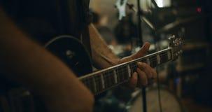 primo piano 4K delle dita che giocano una chitarra elettrica in uno studio domestico stock footage