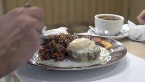 Primo piano 4K l'uomo mangia il riso rosso con la bistecca e l'uovo di manzo affogati, con le verdure fotografie stock
