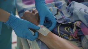 Primo piano L'infermiere completa l'installazione di un catetere del contagoccia stock footage