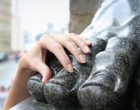 Primo piano la mano di una donna sulla statua del piede Fotografia Stock Libera da Diritti
