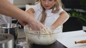 Primo piano La piccola ragazza caucasica con ha pastella mescolantesi della madre in una ciotola di vetro Le mani della bambina e stock footage