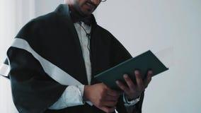 Primo piano, laureato indiano dell'accademia in abito che tiene un diploma e che lo esamina stock footage